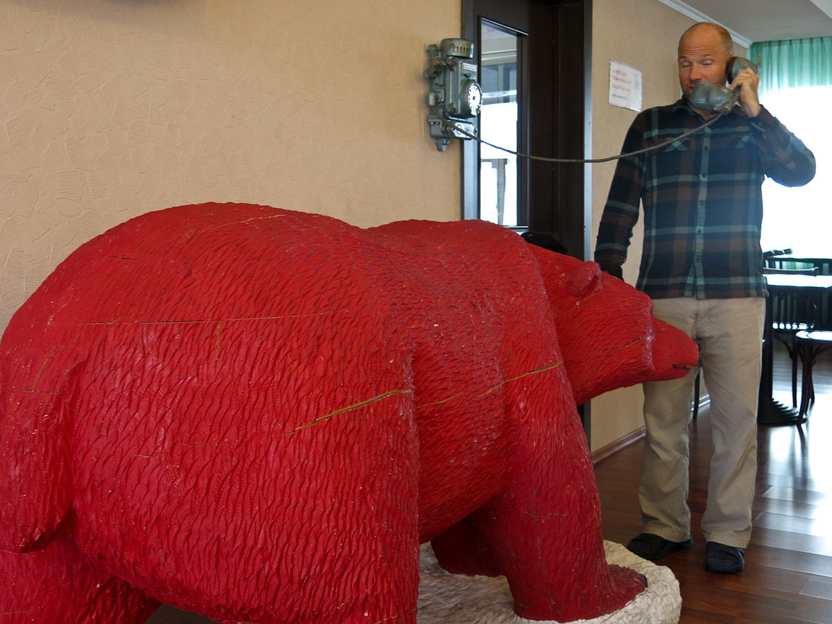 Willie chatting on the phone while a huge red bear sniffs his, uhmm, pants.