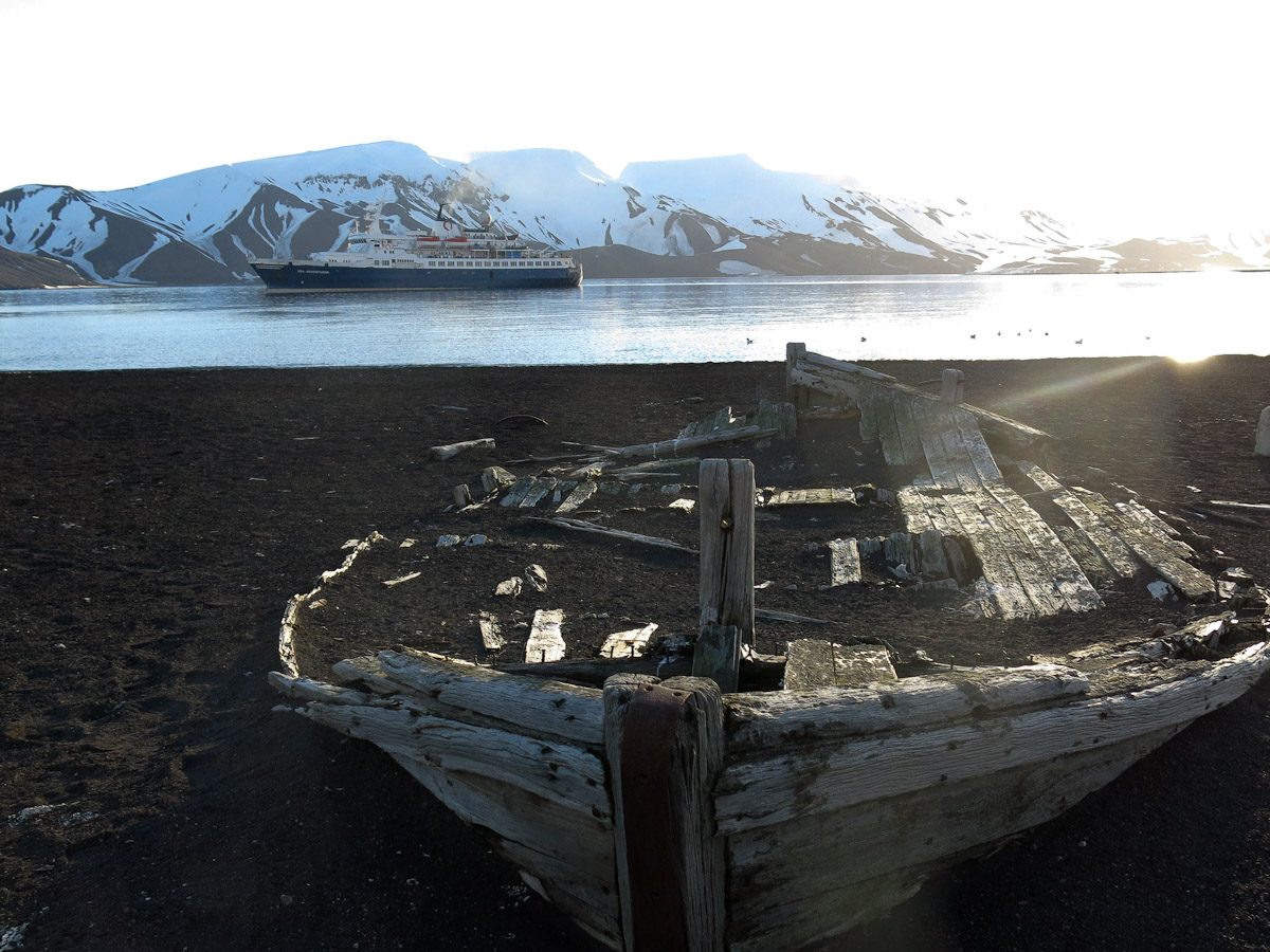 A water boat on Deception Island with the Sea Adventurer behind.